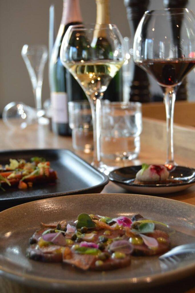 Alkuruoka-annoksia ja viiniä katettuna ravintola Frejan pöytään Espoossa.